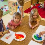 Toddlers painting at our daycare center