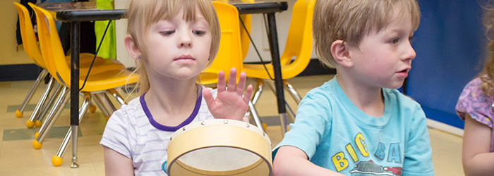Preschooler learning to play a musical instrument in our daycare program.