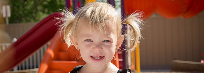 Toddler with pigtails enjoying outdoor playtime.