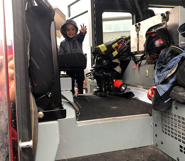 happy toddler plays in a firetruck at our daycare center