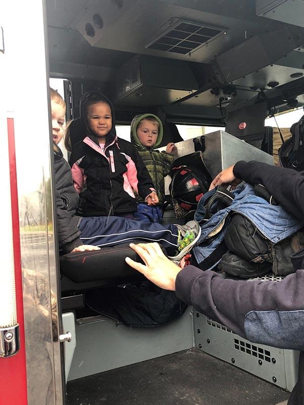 three kids sit in a firetruck