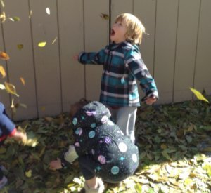 boy playing in leaves at child care center short