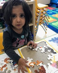 girl solving a puzzle at daycare short